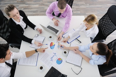 board meeting: Group of young business people sitting in board room during meeting and discussing with paperwork