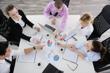 sala de reuniones: Grupo de j�venes empresarios que se sientan en sala de juntas durante la reuni�n y discutir con el papeleo