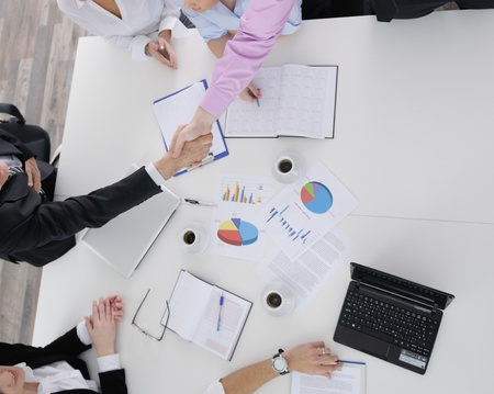 Group of young business people sitting in board room during meeting and discussing with paperwork Stock Photo - 12565240