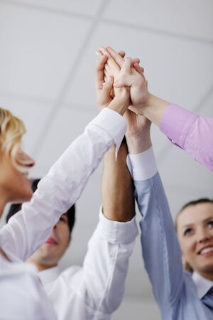 joining hands: business people group joining hands and representing concept of friendship and teamwork,  low angle view