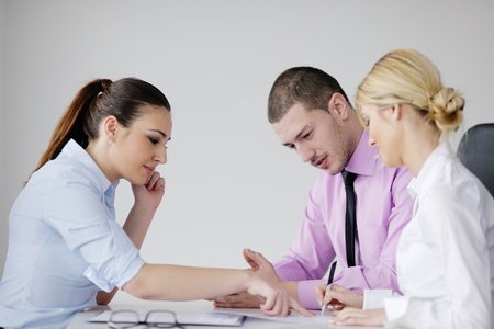 Group of young business people sitting in board room during meeting and discussing with paperwork Stock Photo - 12565161