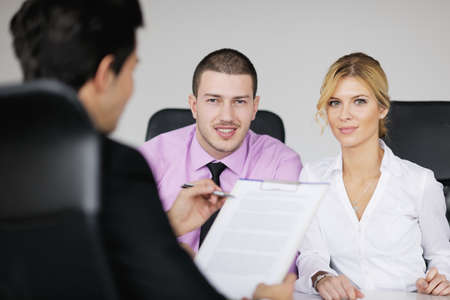 Group of young business people sitting in board room during meeting and discussing with paperwork Stock Photo - 12565157
