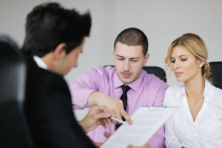 Group of young business people sitting in board room during meeting and discussing with paperwork Stock Photo - 12565139
