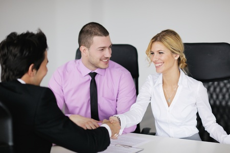 Group of young business people sitting in board room during meeting and discussing with paperwork Stock Photo - 12565213