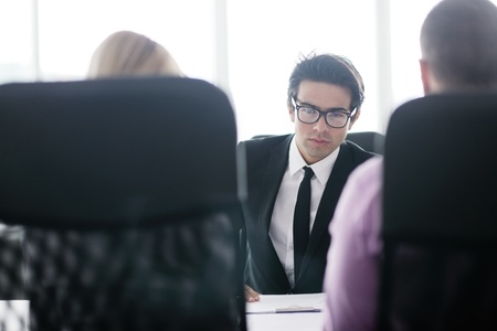 Confident young business man attending a meeting with his colleagues Stock Photo - 12565232
