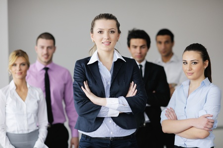 Successful business woman standing with her staff in background at modern bright office Stock Photo - 12565146