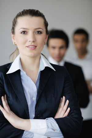 Successful business woman standing with her staff in background at modern bright office Stock Photo - 12565134
