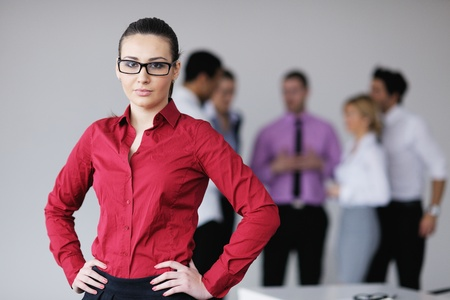 Successful business woman standing with her staff in background at modern bright office Stock Photo - 12565131