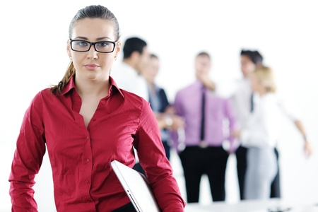 Successful business woman standing with her staff in background at modern bright office Stock Photo - 12565214
