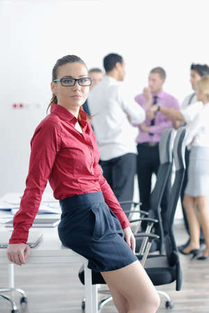 Successful business woman standing with her staff in background at modern bright office Stock Photo - 12565171