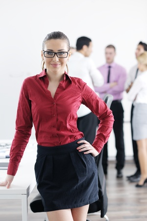 Successful business woman standing with her staff in background at modern bright office Stock Photo - 12565150