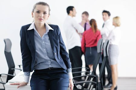 Successful business woman standing with her staff in background at modern bright office Stock Photo - 12565153