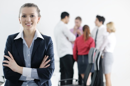 Successful business woman standing with her staff in background at modern bright office Stock Photo - 12565184