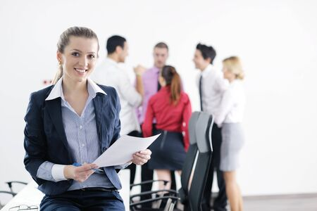 Successful business woman standing with her staff in background at modern bright office Stock Photo - 12565173