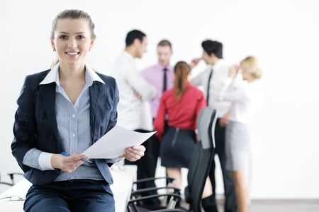 Successful business woman standing with her staff in background at modern bright office Stock Photo - 12565177