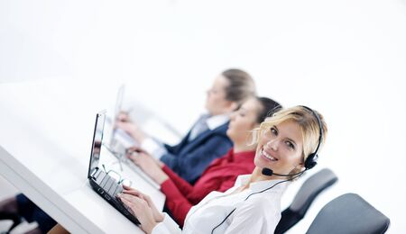 call center female: Pretty young business woman group with headphones smiling at you against white background