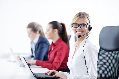 Mooie jonge zakenvrouw groep met hoofdtelefoon glimlachend op je tegen de witte achtergrond