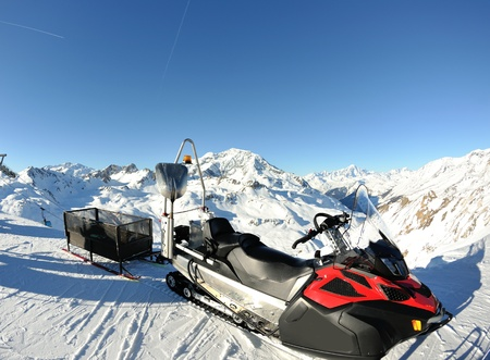 snow mobile sledge parked at mountaint top at beautiful winter sunny day