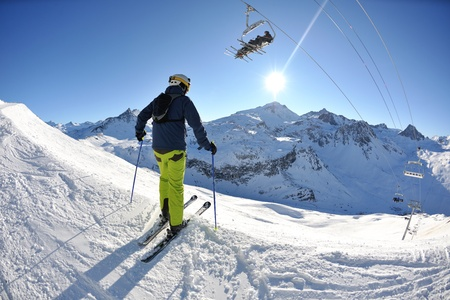 active holiday: skier skiing downhill on fresh powder snow  with sun and mountains in background