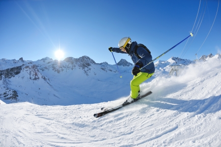 downhill skiing: skier skiing downhill on fresh powder snow  with sun and mountains in background