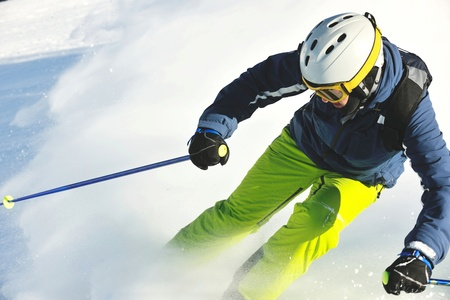 skier skiing downhill on fresh powder snow  with sun and mountains in background Stock Photo - 12565149