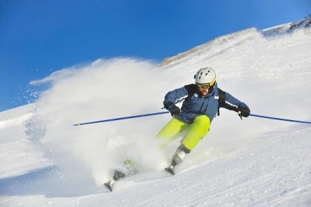 ski�r: skier ski afdaling op verse poedersneeuw met zon en bergen op de achtergrond