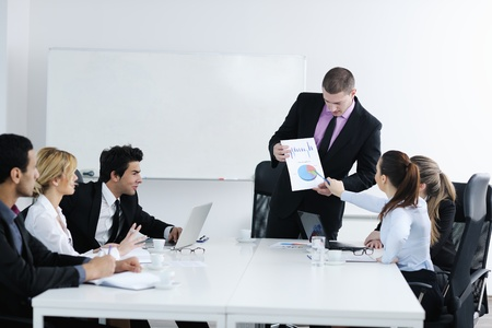 corporate training: Group of young business people sitting in board room during meeting and discussing with paperwork