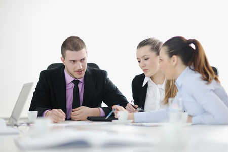 Group of young business people sitting in board room during meeting and discussing with paperwork Stock Photo - 12567561