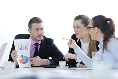 Group of young business people sitting in board room during meeting and discussing with paperwork Stock Photo - 12567691