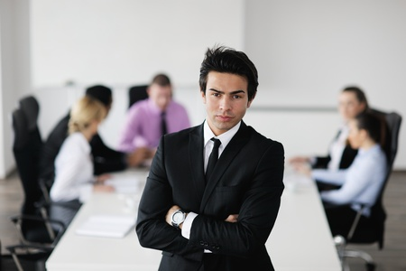 Confident young business man attending a meeting with his colleagues photo