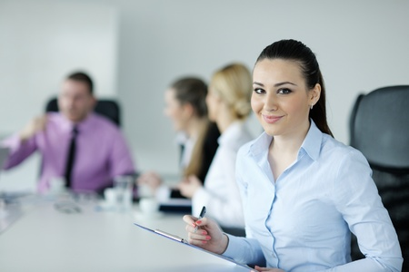 Successful business woman standing with her staff in background at modern bright office Stock Photo - 12567687