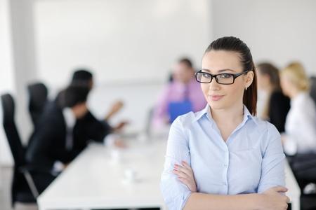 近代的な明るいオフィスでバック グラウンドでの彼女のスタッフで立っている成功したビジネスウーマン