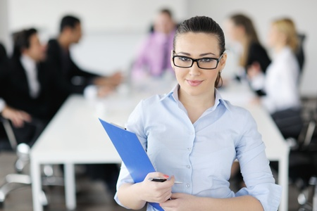 Successful business woman standing with her staff in background at modern bright office Stock Photo - 12567542