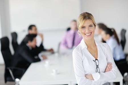 Femme d'affaires réussie debout avec son personnel en arrière-plan au bureau moderne et lumineuse Banque d'images