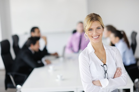 Successful business woman standing with her staff in background at modern bright office Stock Photo - 12567789