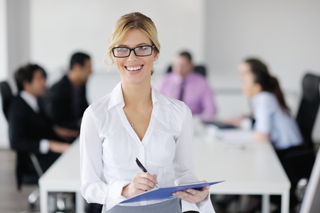 Successful business woman standing with her staff in background at modern bright office Stock Photo - 12567872