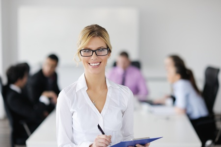 Successful business woman standing with her staff in background at modern bright office Stock Photo - 12567585