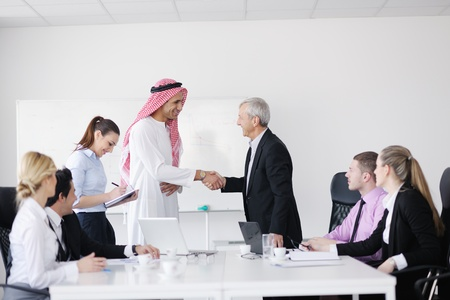 Business meeting - Handsome young Arabic  man presenting his ideas to colleagues and listening for ideas for success investments at bright modern office room Stock Photo - 12567704