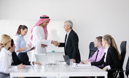 arab girl: Business meeting - Handsome young Arabic  man presenting his ideas to colleagues and listening for ideas for success investments at bright modern office room