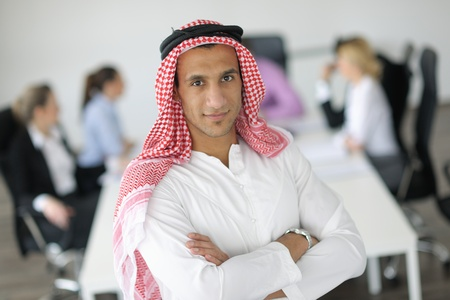 Business meeting - Handsome young Arabic  man presenting his ideas to colleagues and listening for ideas for success investments at bright modern office room Stock Photo - 12567934