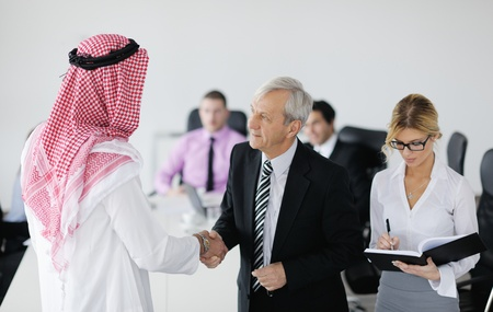 Business meeting - Handsome young Arabic  man presenting his ideas to colleagues and listening for ideas for success investments at bright modern office room Stock Photo - 12567942