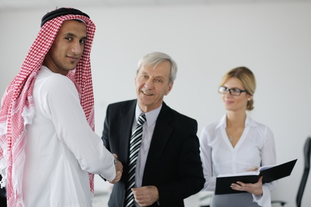 Business meeting - Handsome young Arabic  man presenting his ideas to colleagues and listening for ideas for success investments at bright modern office room Stock Photo - 12567986