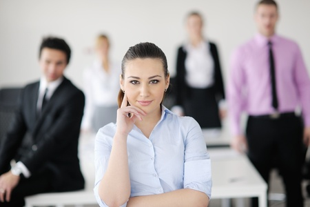 Successful business woman standing with her staff in background at modern bright office Stock Photo - 12567938