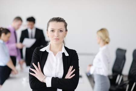 Successful business woman standing with her staff in background at modern bright office Stock Photo - 12567748