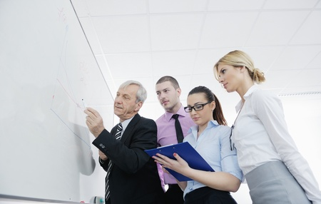 Senior male business man giving a presentation at a  meeting at modern light office on a table board photo