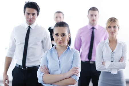 Successful business woman standing with her staff in background at modern bright office Stock Photo - 12567941