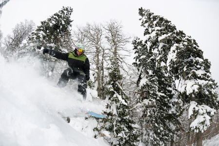 extreme danger: Snowboarder doing a jump and free ride on  powder snow at winter season