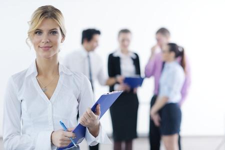 gerente: Exitosa mujer de negocios de pie con su bastón en el fondo brillante de la oficina moderna