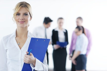 Successful business woman standing with her staff in background at modern bright office photo
