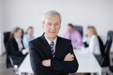 senior ordinateur: �quipe de gens d'affaires lors d'une r�union dans un environnement de bureau l�ger et moderne.